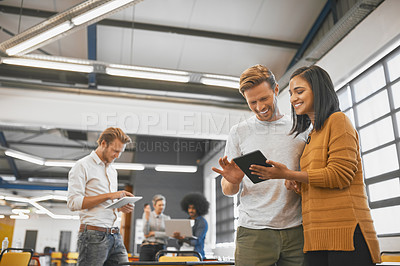Buy stock photo Cropped shot of two young businesspeople looking at a tablet in the office with their colleagues in the background