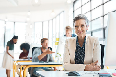 Buy stock photo Portrait of a happy designer sitting at her desk while her colleagues work in the background