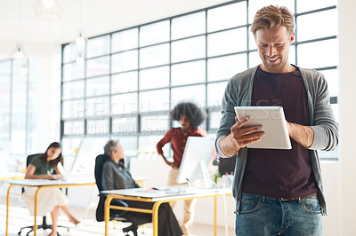 Buy stock photo Shot of a happy designer using his tablet in the office while his colleagues work in the background