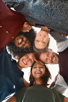 Buy stock photo Low-angle portrait of a team of happy designers posing with their heads in a huddle in the office