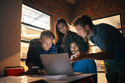 Buy stock photo Shot of a group of designers working together on a laptop
