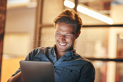 Buy stock photo Shot of a handsome young man working late in his office