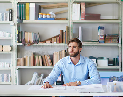 Buy stock photo Cropped shot of a handsome young male architect sitting in his office