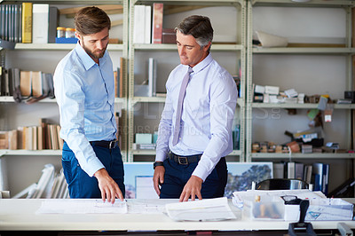 Buy stock photo Cropped shot of two male architects looking over some blueprints in the office