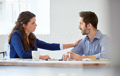Buy stock photo Cropped shot of an attractive young businesswoman reassuring a male colleague in the office