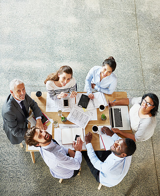 Buy stock photo High angle portrait of a group of businesspeople working while sitting around in a table