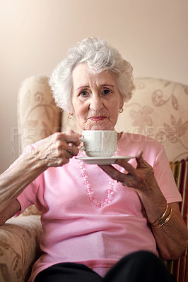 Buy stock photo Portrait of a senior woman having a warm beverage on a chair at home