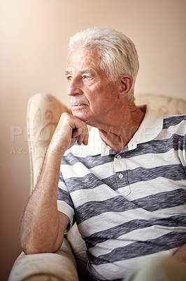 Buy stock photo Shot of a senior man sitting on a chair and looking thoughtful at home