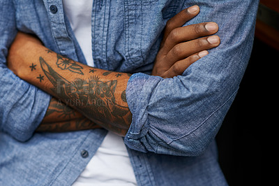 Buy stock photo Shot of an unidentifiable man with tattoos on his arms standing outside