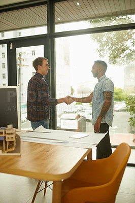 Buy stock photo Shot of two young designers shaking hands in an office