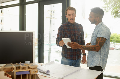 Buy stock photo Shot of two young architects working together on a digital tablet in an office