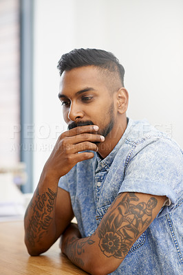 Buy stock photo Shot of a young designer looking thoughtful while sitting in an office