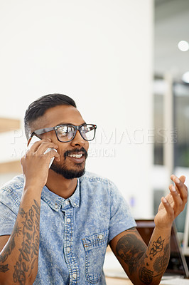 Buy stock photo Shot of a young designer talking on a cellphone in an office