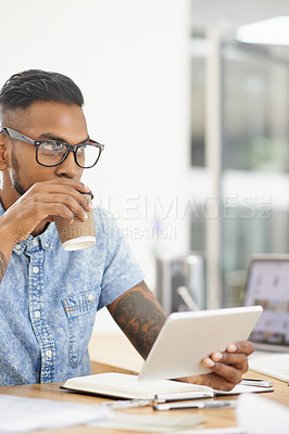 Buy stock photo Shot of a young designer drinking coffee while working on a digital tablet in an office