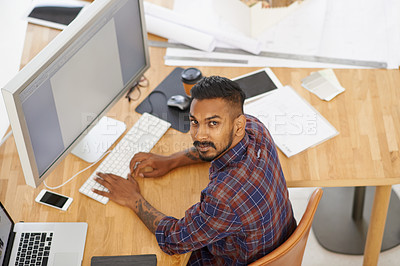 Buy stock photo High angle portrait of a young designer working at his desk in the office
