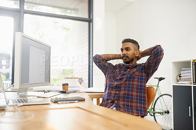 Buy stock photo Shot of an easygoing young designer working at his desk in the office