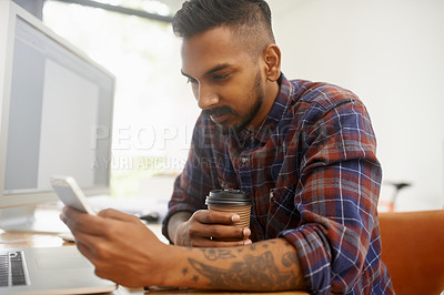 Buy stock photo Shot of a young designer using his smartphone while drinking coffee at his desk in the office