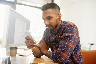 Buy stock photo Shot of a young designer using his smartphone while sitting at his desk in the office