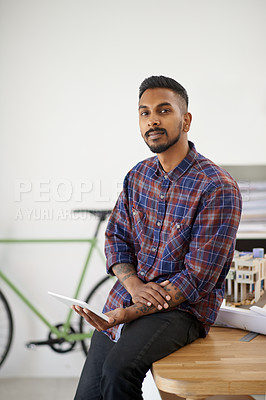 Buy stock photo Portrait of a creative young designer using his tablet while leaning on his desk in the office