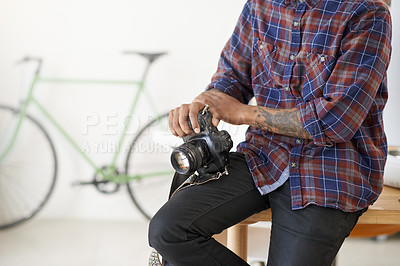 Buy stock photo Shot of an unidentifiable young photographer holding his camera while leaning on his desk in the office
