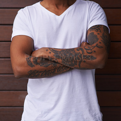 Buy stock photo Shot of an unidentifiable man with tattoos on his arms posing against a brown background outside