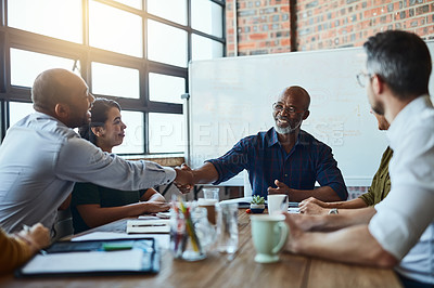 Buy stock photo Cropped shot of a group of business colleagues in the office shaking hands in agreement on a certain idea