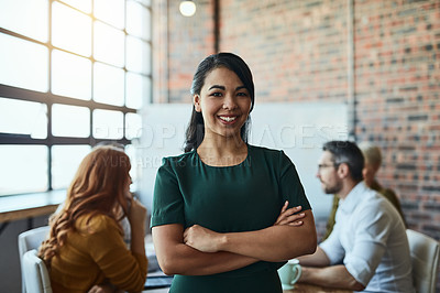 Buy stock photo Cropped shot of a businesswoman standing in the office with her arms folded looking confident and smiling at the camera