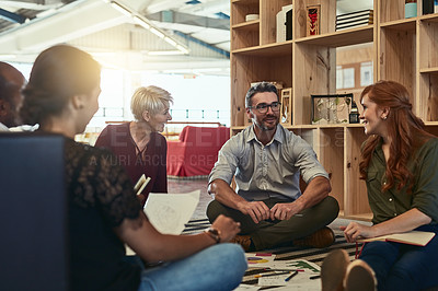 Buy stock photo Cropped shot of a group of business colleagues in the office sitting on the floor and discussing ideas