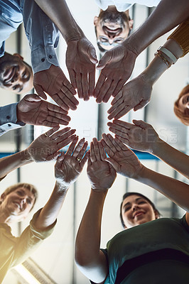 Buy stock photo Low angle shot of a group of colleagues joining their hands in solidarity at work