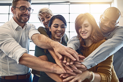 Buy stock photo Shot of a group of colleagues joining their hands in solidarity at work