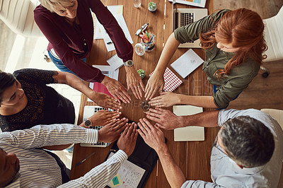 Buy stock photo High angle shot of a group of colleagues joining their hands in solidarity during a meeting in a modern office