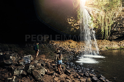Buy stock photo Shot of two female friends walking towards a waterfall outdoors
