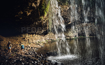 Buy stock photo Shot of two young female friends walking underneath a waterfall looking where to go