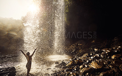 Buy stock photo Rearview shot of a young woman arms raised underneath a waterfall enjoying a day in nature