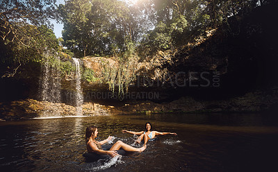 Buy stock photo Shot of two young women enjoying the lovely water by a waterfall in nature