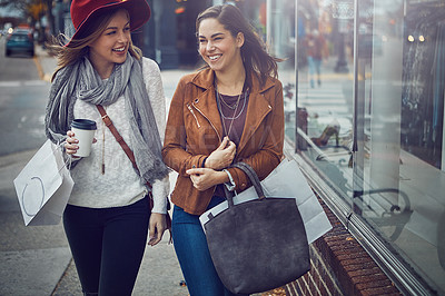 Buy stock photo Cropped shot of two young girlfriends walking around downtown while on a shopping spree
