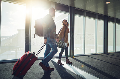 Buy stock photo Shot of a young couple walking together in an airport with their luggage while holding hands
