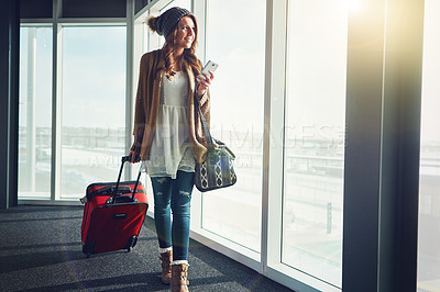 Buy stock photo Shot of a young woman standing in an airport with her luggage staring outside and holding her cellphone