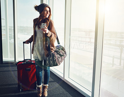 Buy stock photo Shot of a young woman standing in an airport with her luggage staring outside while holding her cellphone