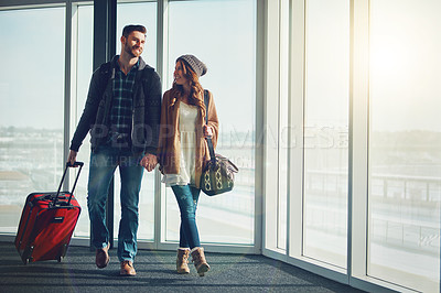 Buy stock photo Shot of a young couple walking inside of an airport with their luggage and holding hands