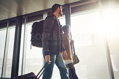 Buy stock photo Shot of a young couple walking inside of an airport with their luggage and holding hands while looking outside