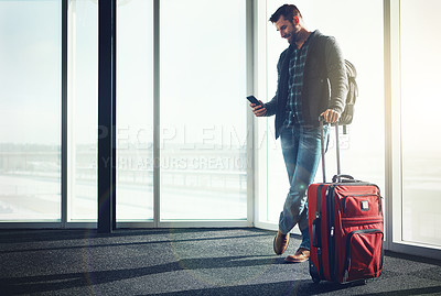 Buy stock photo Shot of a young man standing in an airport with luggage and looking at his cellphone