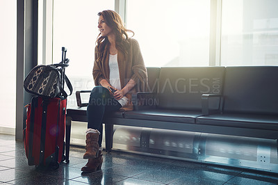 Buy stock photo Shot of a young woman sitting in an airport wth her luggage while holding her cellphone and looking at someone