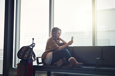 Buy stock photo Shot of a young woman sitting in an airport with her luggage and holding her cellphone and taking a picture