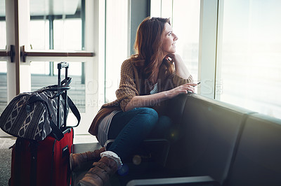 Buy stock photo Shot of a young woman sitting inside of an airport with her luggage and holding her cellphone while looking outside