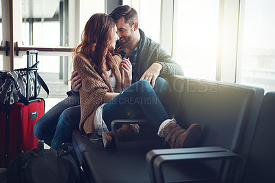 Buy stock photo Shot of a young couple sitting in an airport with their luggage and embracing each other