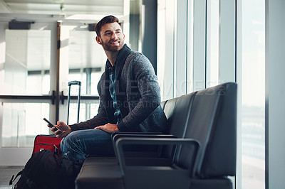 Buy stock photo Shot of a young man sitting in an airport with his luggage while holding his cellphone and looking at something