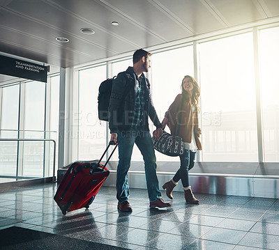 Buy stock photo Shot of a young couple walking in an airport with their luggage while holding hands and looking at one another