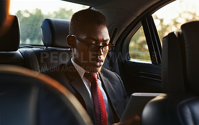 Buy stock photo Shot of a focussed young businessman using his tablet while traveling in the back of a car