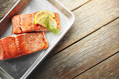 Buy stock photo Shot of a piece of fish garnished with slices of lemon and fresh leaves in a dish